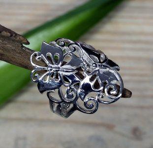 Echt zilveren (925) vlinder ring. Sierlijke opengewerkte ring met twee vlinders en een krullen-motief. De ring sluit mooi aan om de vinger.  Lengte van de vlinders 27 mm. Breedte onderkant ring op...