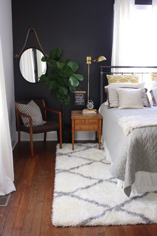 Dark accent wall, in a bedroom with a lot of natural light and hardwood floor. The rug in this room is everything. The plant and the small nightstand with a mirror and chair tucked in the corner ad a great homey touch. A place to sit in the room other than the bed is always good to have.