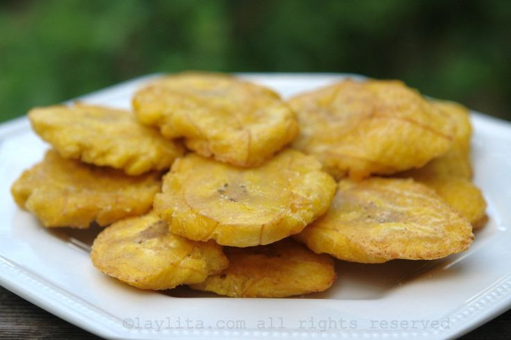 Easy recipe for homemade patacones or tostones, a popular Latin American appetizer or side dish made with twice fried slices of green plantains.