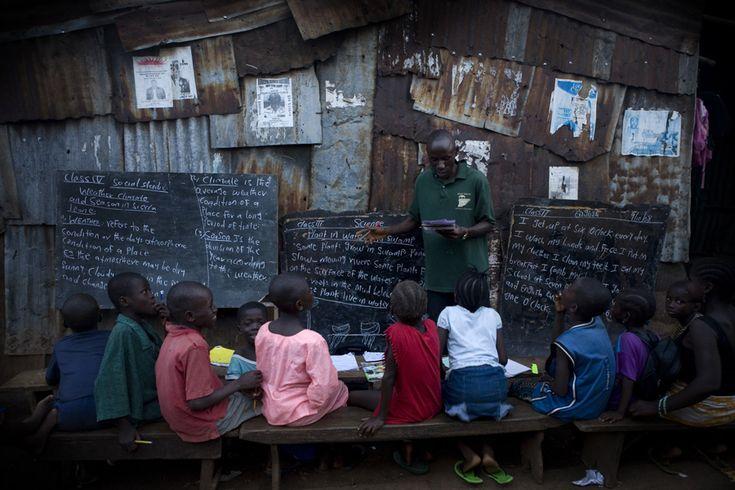 A class is taught in a narrow passage in Kroo Bay slum. Kroo Bay, Freetown, Sierra Leone.