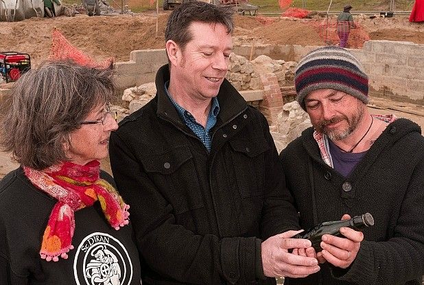 Chris Knight from @Stéphane Rasselet Austell Brewery with Eileen Carter and James Gossip of the St Piran Trust and the 1910 bottle of Walter Hicks ale found at St Piran's Oratory, which is being dug from the dunes above Perranporth in Cornwall.