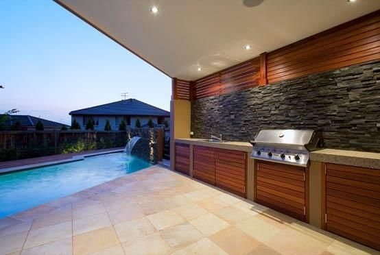 Outdoor kitchen with BBQ near swimming pool