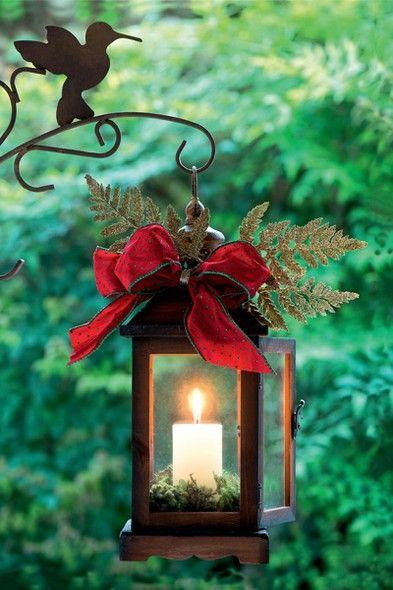 Um laço vermelho e alguns galhinhos já são o suficiente para dar um toque natalino à lanterna de ferro. Um ninho de musgos completa a decoração #christmas #natal #navidad | Christmas decor