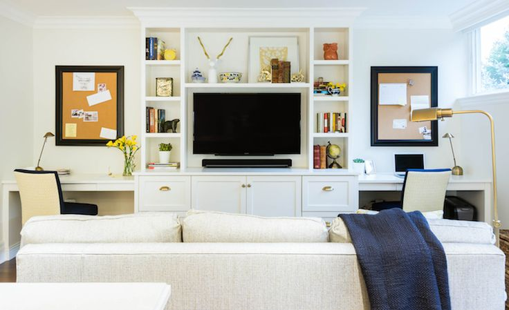 Lovely family room centers on a built-in tv media center flanked by built-in desks below framed cork boards paired with ivory and navy desk chairs tucked below the counters on either side across from an tweed sofa illuminated by a brass bankers floor lamp.