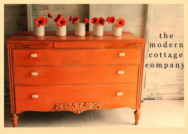 The Modern Cottage Company. Orange dresser painted in Annie Sloan Chalk Paint Barcelona Orange, Anthropologie knobs, MMS white wax.