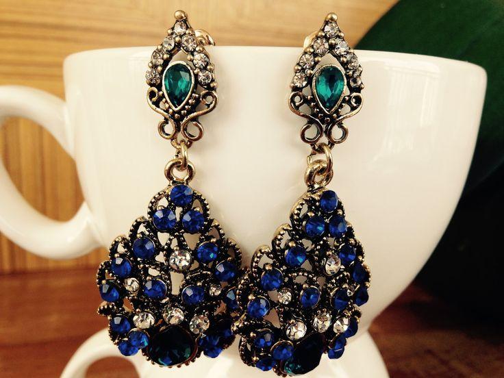 Brinco em bijuteria com acabamento ouro velho e aplicação de strass e cristais nas cores azul anil e turquesa