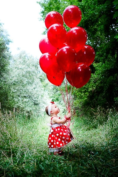 Adorable little girl with a balloon bouquet....all in red!