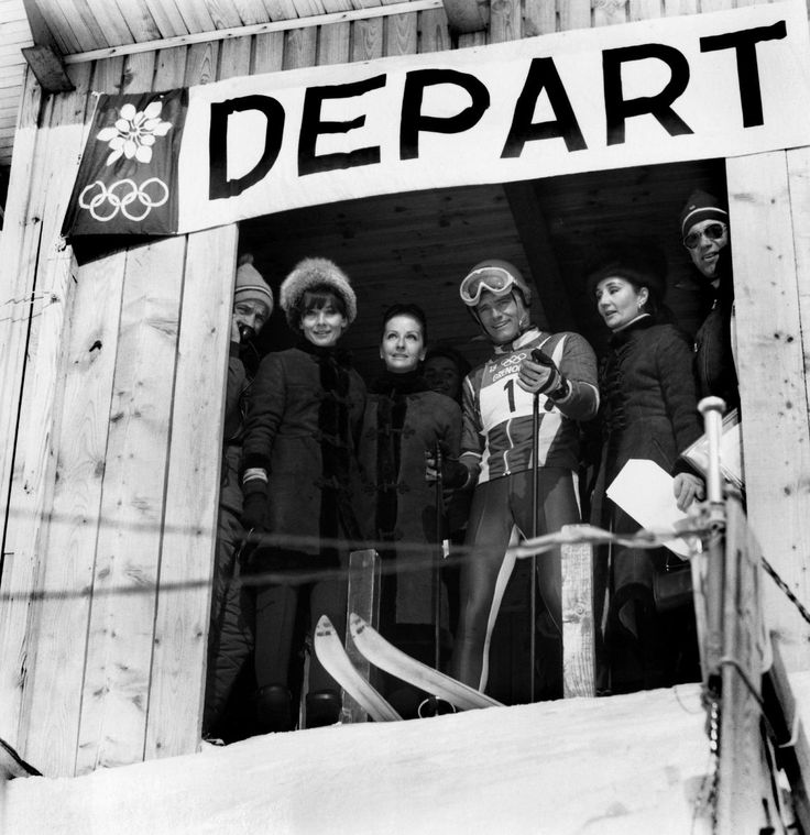 The actor Yul Brynner, his wife Doris, Audrey Hepburn, and the Countess Jacqueline de Ribes pose with Olympic skier Jean-Claude Killy in Chamrousse (near Grenoble, in the French Alps), during the Winter Olympic Games on February 14, 1968.  Audrey and Doris are wearing the same model of a Givenchy coat of brown suede with fur details, created first for Audrey, in 1964.