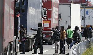 I migranti si riuniscono nei pressi di una linea di camion a Calais