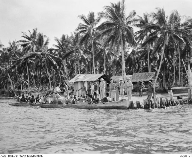 Native scouts about to set out in a canoe with a USMC intelligence patrol from the secret Coastwatchers stronghold at SEGI, Solomon islands. Farewelling the party are (L to R), Cpt D. Kennedy, British Solomon Is. Protectorate Defence Force; Lt W.F. Coultas, USMC; Probably Cpt Boyd, USMC; Lt A.R. Evans, Royal Australlian Navy Volunteer Reserve; & Lt Carsen, US Navy Reserve