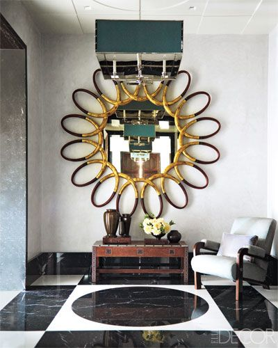 Manhattan entryway with an oversize 1960s gilt-wood mirror and a graphic marble floor.