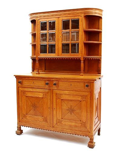Oak Nieuwe Kunst cabinet with two doors below two drawers the upper part with a two-door vitrine cabinet flanked by shelves the doors and drawers carved with floral patterns the upper part decorated with a rim of shell ornaments and geometrical patterns designer execution unknown the Netherlands ca.1900