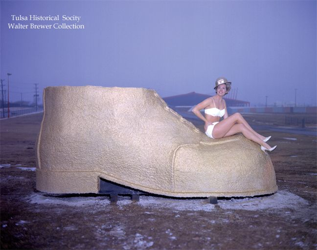 An unidentified model posed on one of the Golden Driller's shoes, probably sometime during construction of the permanent version in time for the 1966 petroleum expo. Description from aoghs.org. I searched for this on bing.com/images