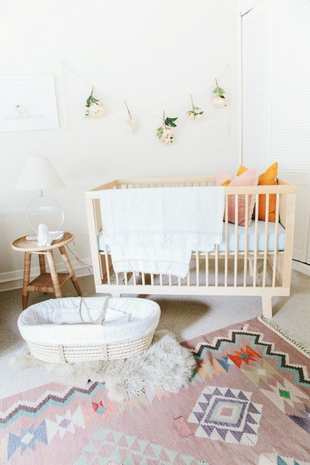 A garland of silk flowers is a simple route to sweet baby décor. Soft pastels mixed with earthy textures create a modern update to the usual baby-girl colour palette.