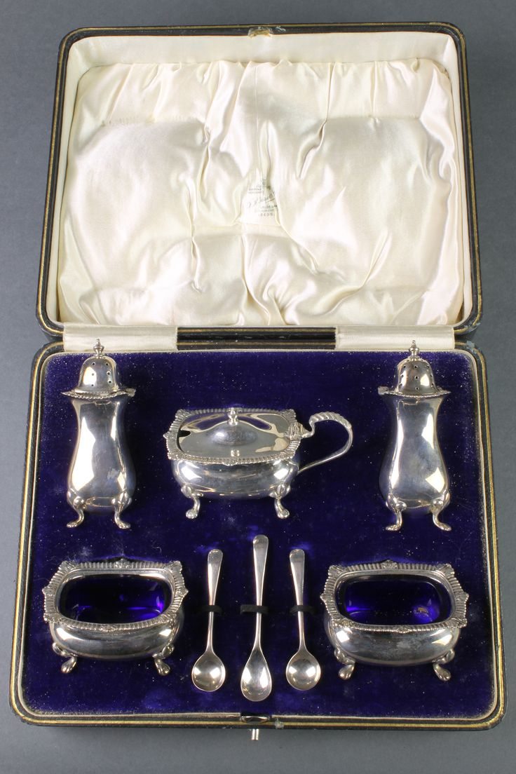 Lot 570, A cased silver 8 piece condiment set with gadrooned decoration, raised on pad feet, Birmingham 1922, 244 grams, sold for £190