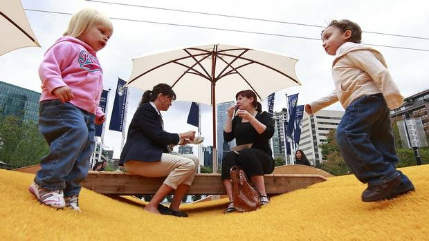 Bobbie Charette, left, and Josie Hoi picnic as children play during the lunch hour at the Picnurbia installation in Robson Square in Vancouver, Aug. 10, 2011. Picnurbia, a pop up picnic zone between Robson Square and the Vancouver Art Gallery, has bright yellow artificial turf, grassy hills, beach umbrellas and built-in benches. (Jeff Vinnick/The Globe and Mail /Jeff Vinnick/The Globe and Mail)