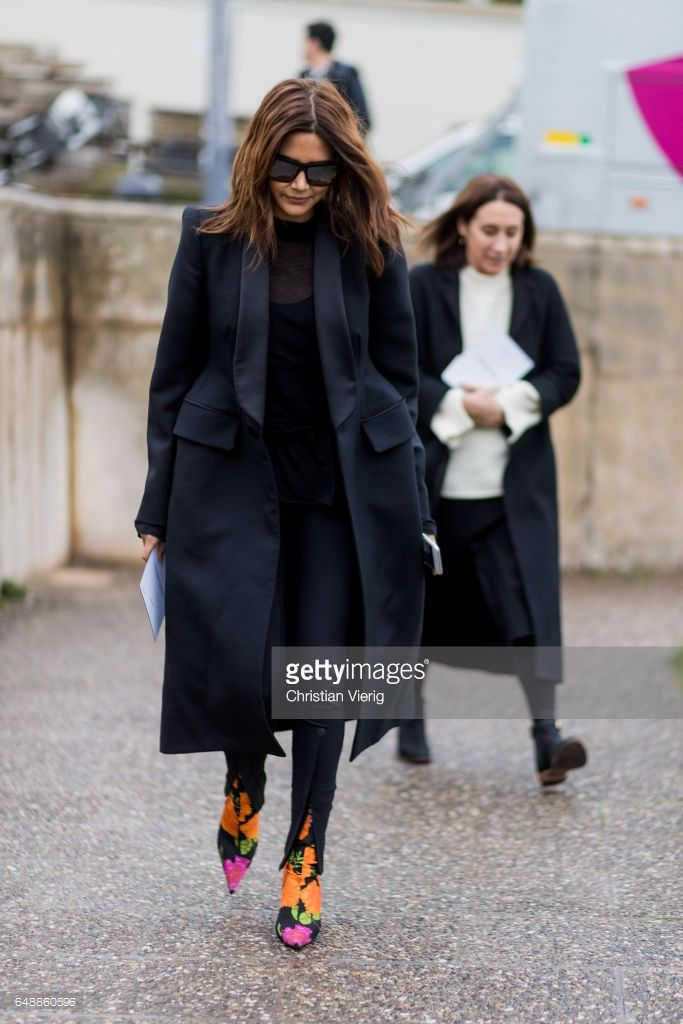 Christine Centenera wearing a black coat, multi coloured ankle boots outside Hermes on March 6, 2017 in Paris, France.