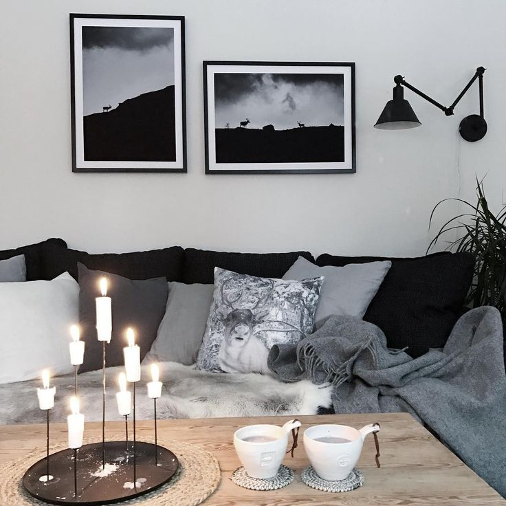 Cosy scandinavian living room with candlestick, lots of cushions and framed posters from printler.com, the marketplace for photo art.