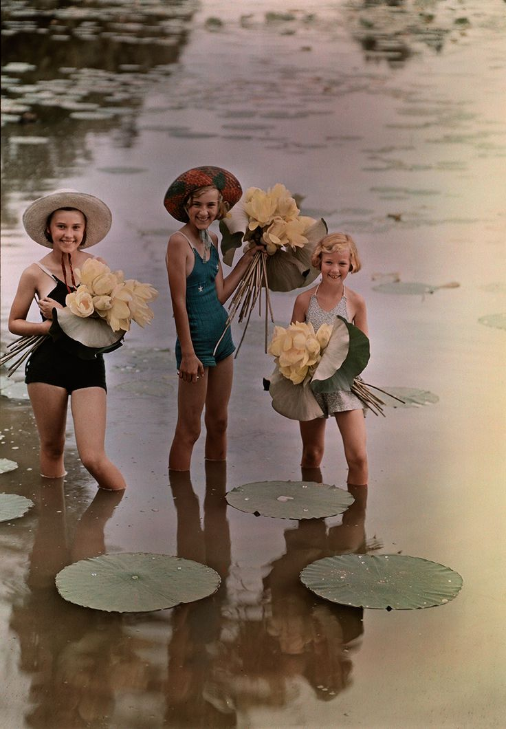 Girls standing in water holding bunches of American Lotus, Amana, Iowa, November 1938.