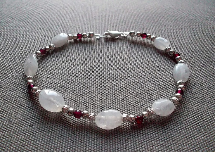 Handcrafted bracelet featuring 10mm oval shaped genuine moonstone beads, 3mm round genuine garnet beads, and 3mm sterling silver beads and clasp. 8 inches in length.