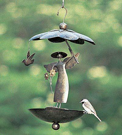 """Nuestro jardín Ángel del alimentador del pájaro está hecho a mano en Bali de acero sólido con un acabado en bronce envejecido resistente a la intemperie. Ella sostiene un paraguas en una mano y una flor en la otra como una paloma vuela por. Agujeros Paraguas y drenaje en la parte inferior mantienen la semilla seca. Tamaño 9-1/4 """"de diámetro. x 16-1/4"""" H garden angel bird feeder"""