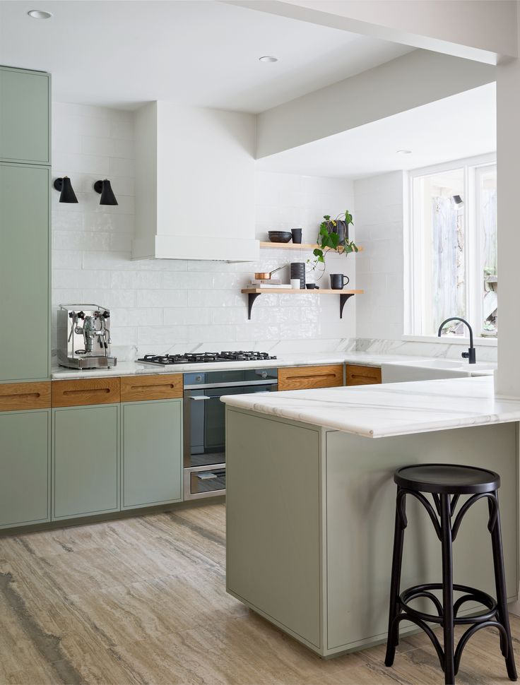 A clean and fresh-looking kitchen remodel with sage kitchen cabinets, Calacatta…