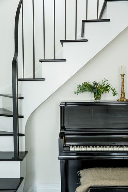 Black upright piano nestled under stairs