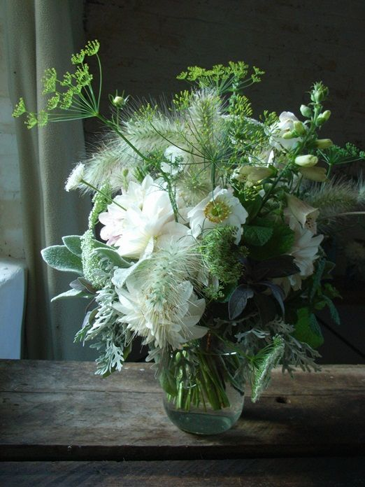 A white and green flower arrangement with dill flowers, furry grasses, white dahlias and a single white foxglove