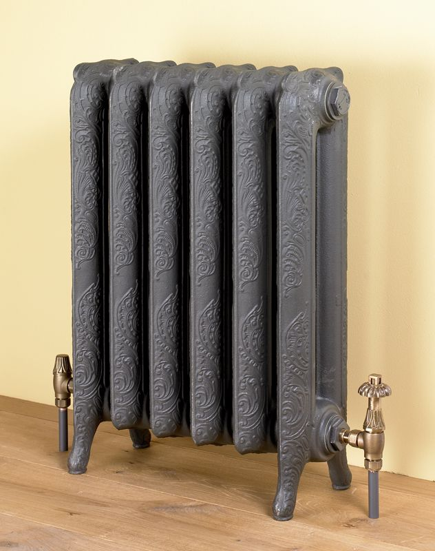 The Liberty cast iron radiator features in the Victorian hallway against a dark red wall.