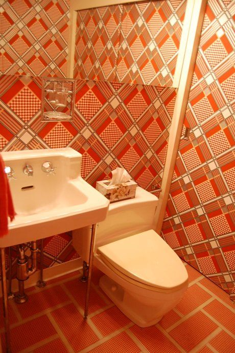 Here is the downstairs powder room. It has very 70s wallpaper — on the walls, the closet doors and the ceiling. It's kind of interesting to see the mod wallpaper and toilet paired with the classic American Standard 50s sink. Like the idea, but not the color? See http://www.bathroom-paint.net/bathroom-paint-alternatives.php for other possibilities.
