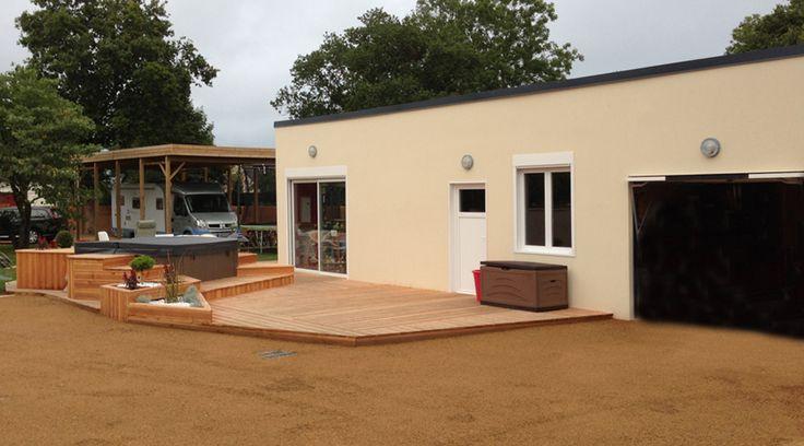 atelier en béton aspect terrasse couverture bac acier avec 1 baie coullissante en alu, une porte pvc vitrée, 1 fenêtre alu avec volet roulant et 1 portail basculant