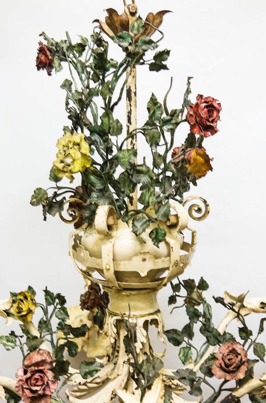 € 1.495,00 - Hele grote oude hanglamp, te dateren rond de jaren 30 ongeveer. Een zogenaamde bloemen-kroonluchter. De lamp heeft 6 armen, die bloemkelken symboliseren. Verder is de lamp op diverse plaatsen versierd met metalen bloemen in roze en gele kleuren. Al met al een hele sierlijke en vrolijke lamp. Deze lamp is niet voor iedereen, je vindt hem vermoedelijk of helemaal te gek of juist niet. Let op; het is wel een hele grote lamp.