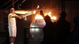 Der brasilianische Marathonläufer Vanderlei Cordeiro de Lima entzündet das Olympische Feuer.