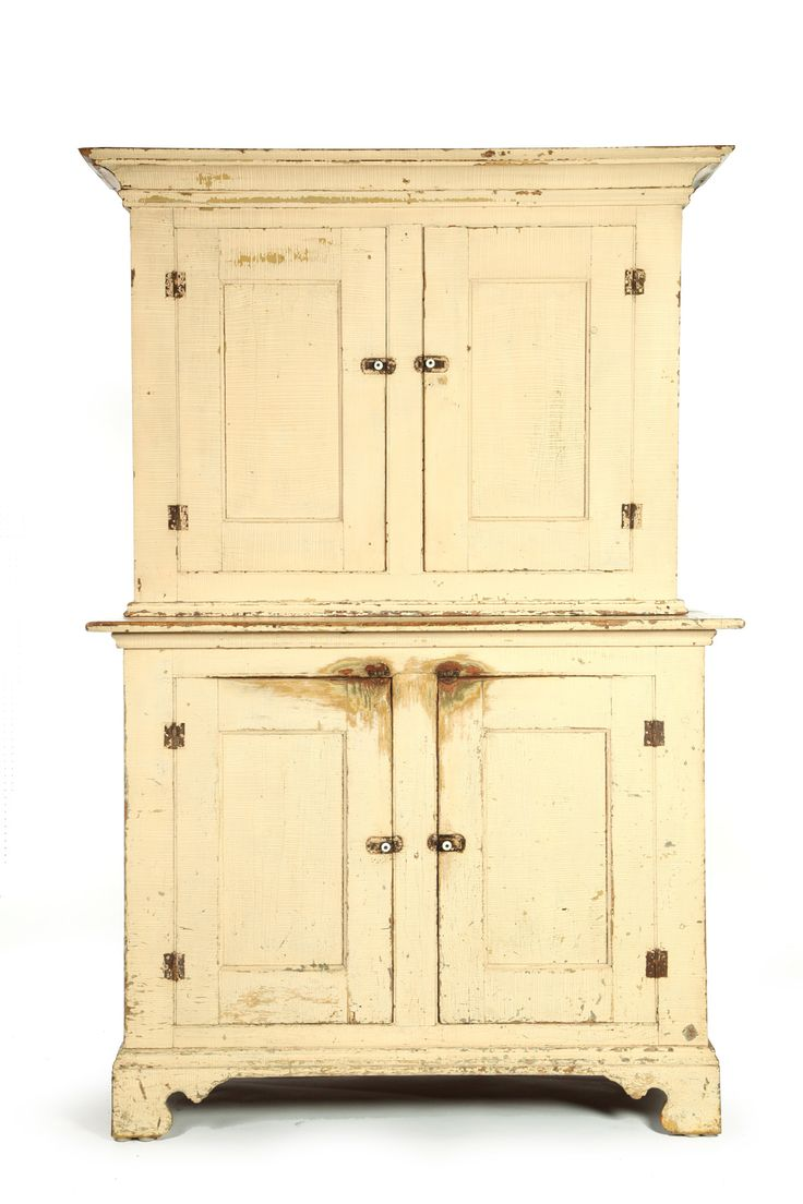 American, mid 19th Century Pine.  Two piece cupboard with blind doors on top and bottom.  Old buttermilk colored paint has wear.  Replaced cornice  Garths Auction