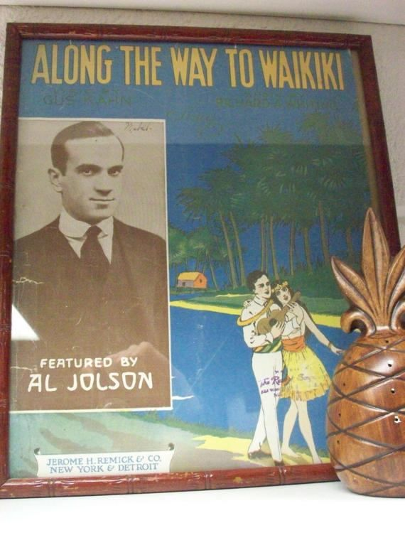 This Hawaiian style sheet music has been framed in a wood bamboo look frame. It would look great in your or tropical inspired room or Tiki bar. The song is titled Along the Way to Waikiki by Al Jolson. From my research I think it dates from the 20s. It shows age related wear to the edges from age but is complete.  The frame measures 13 1/2 by 11 3/4 and the sheet music is 13 1/2 by 10 1/2. The bottom edge was folded under to fit the frame.  There is a saw tooth hanger on t...