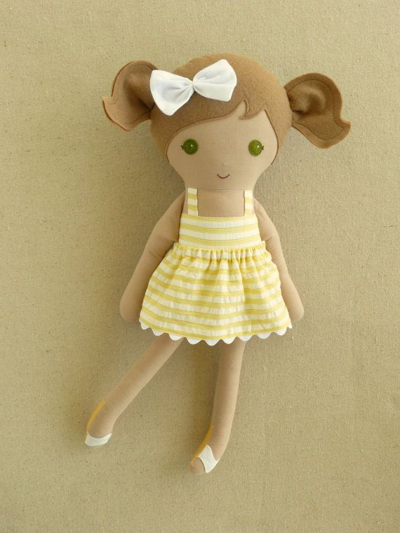 This is a handmade cloth doll measuring 20 inches. She is wearing a sweet yellow and white striped sundress with a matching, removable skirt and