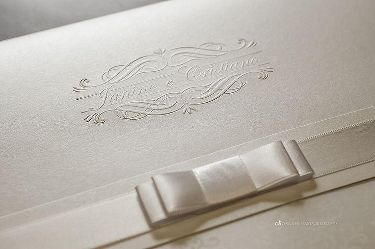 Detalhes do convite de casamento: brasão exclusivo, laço Chanel duplo e cobertura perolada.