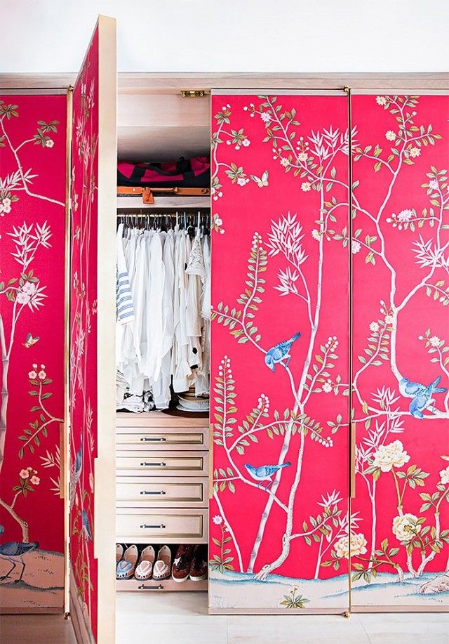 A wardrobe with walls covered in a bright hand-painted wallpaper