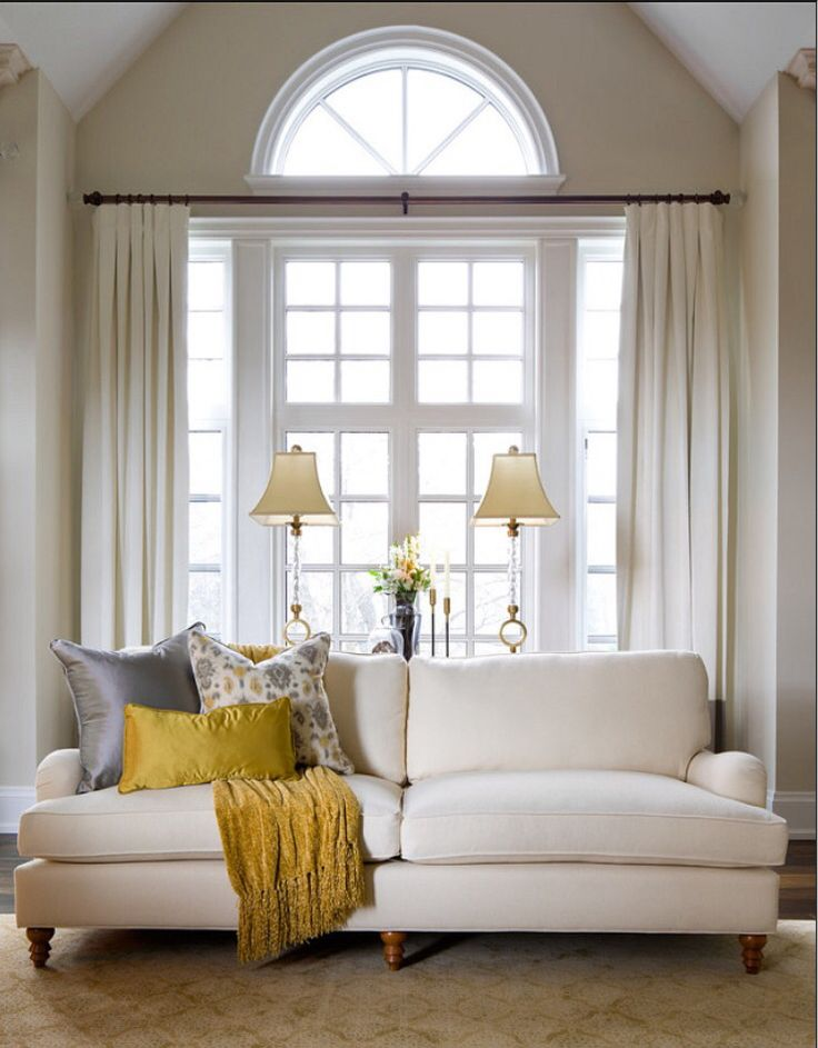 Draperies mounted between the arch and casement windows on an iron rod.