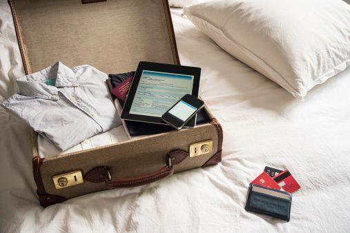 Öffnen Sie Koffer auf Bett mit digitaler Tablette und Handy