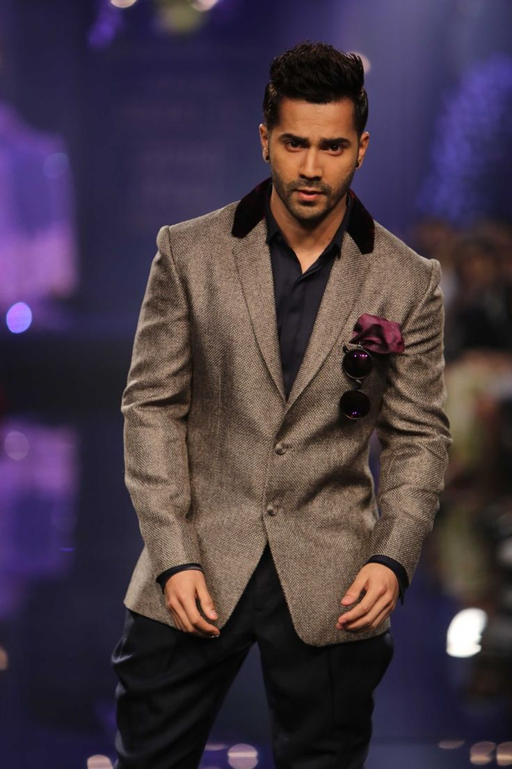 Varun Dhawan in a fitted, grey blazer with black trousers looked elegant and smart. The maroon handkerchief adds some color to the effortlessly chic outfit for men. | Manish Malhotra Lakme Fashion Week
