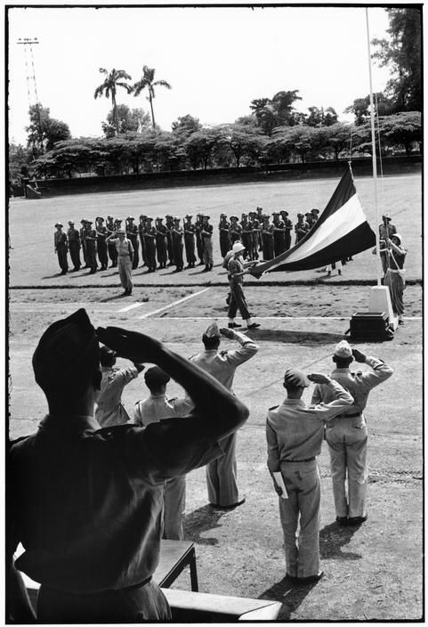 INDONESIA. Java. Solo. 1949. Dutch transfer. Dutch flag comes down and Republic flag goes up at ceremony in town stadium. From Magnum Photos website.