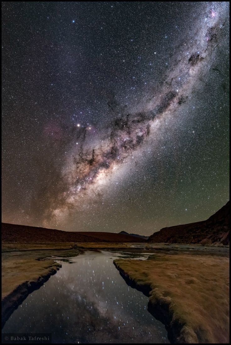 Le fleuve étoilé de Voie lactée, majestueux, se reflétant ici dans les eaux d'une rivière de la région aride de l'Atacama, au Chili, dans l'hémisphère sud. Le renflement central est le centre de notre Galaxie. Un peu au-dessus, nimbés de délicats nuages colorés, on distingue les étoiles du Scorpion (notamment la rouge orangé Antarès). Non loin, les planètes Mars et Saturne sont bien visibles aussi (été 2016) — Crédit : Babak Tafreshi (Twan)