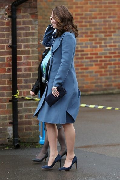 The Duchess of Cambridge was impeccably co-ordinated in a blue coat, navy suede heels and a patterned scarf. She teamed the ensemble with a small navy clutch bag, accessorizing with sapphire earrings