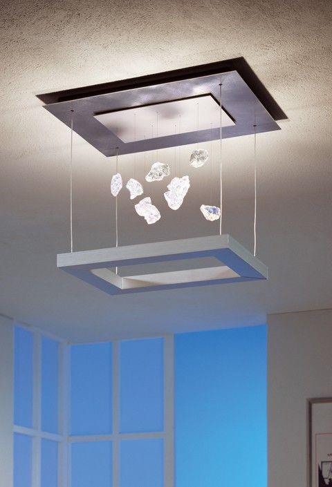 Die Escale Della Luna Cristallo ist eine Deckenleuchte, bestehend aus zwei übereinanderhängenden Rahmen. Von dem oberen Rahmen hängen zudem Kristallglasteile herab. Hochvolt-Halogenlampen dienen als Leuchtmittel