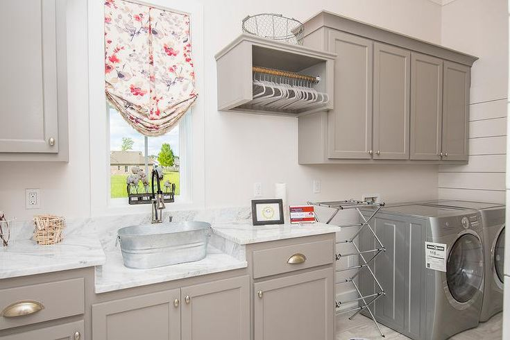 Laundry room features gray cabinets paired with marble countertops lined with an oval bucket sink.