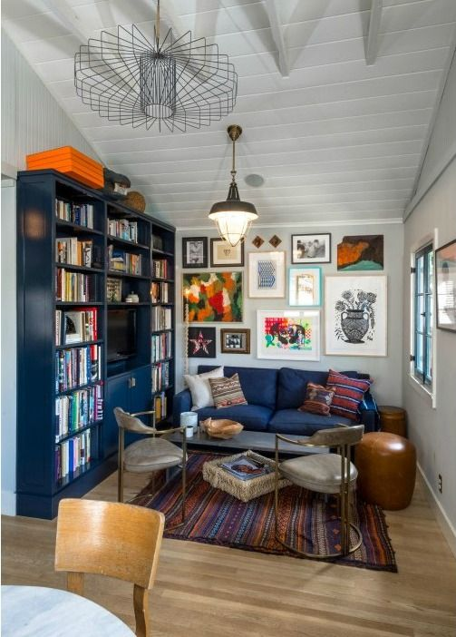 blue bookcases, rug, gallery wall, leather