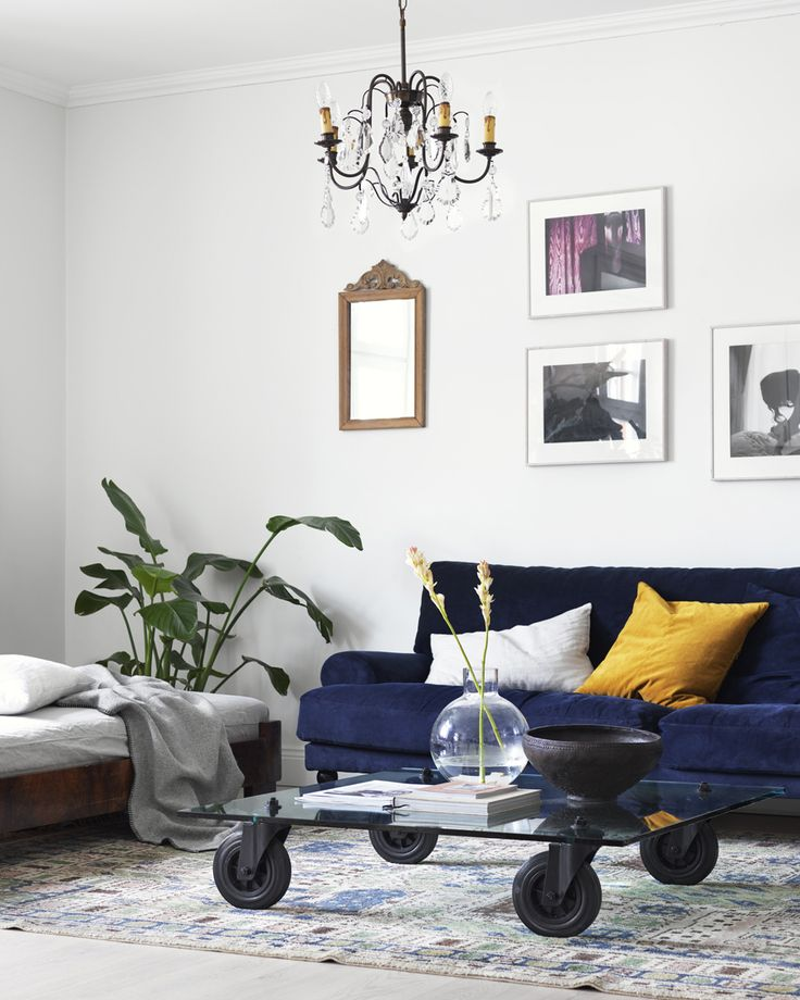 Scandinavian interior styling and ideas how to decorate the blue sofa. Velvet sofa, yellow details.