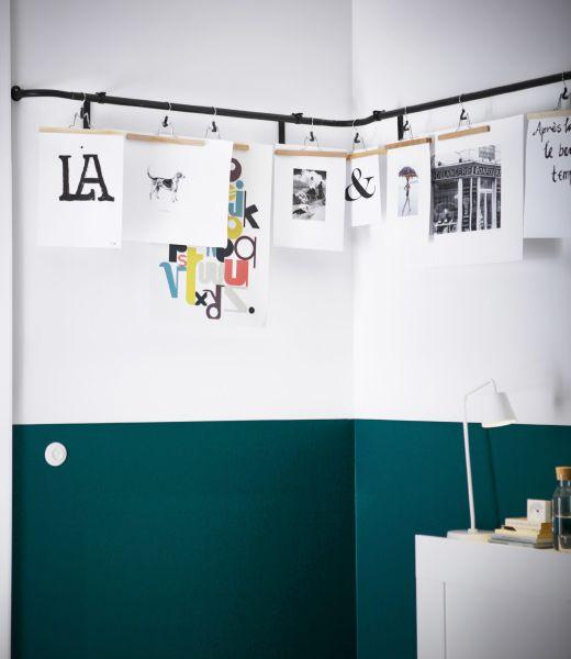 Verschiedene Kunstwerke, die mithilfe von BUMERANG Hosenbügel in Naturfarben an IKEA HUGAD Gardinenstange aufgehängt wurden.