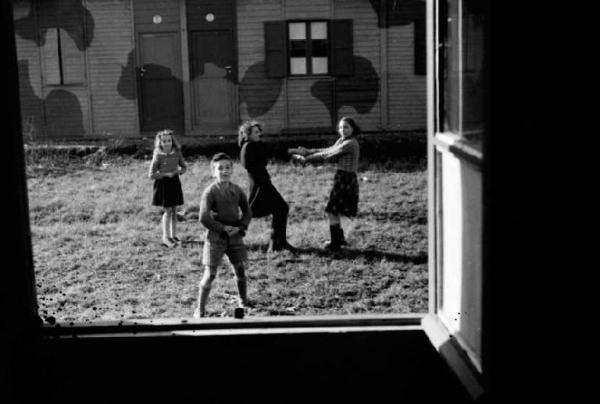 Italia Dopoguerra. Milano. Quartiere Baggio. Gruppo di bambini gioca all'aperto tra le abitazioni prefabbricate.